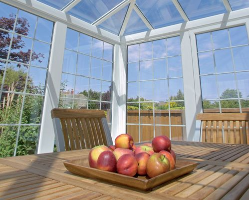 crown conservatory view from the inside out with a table and apples on the table